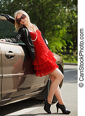 Happy young woman with a new convertible car