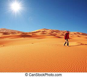 Hiking in desert - man go  in sand desert