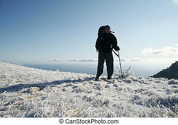 Man overview snow covered landscape - Backpacker overview...