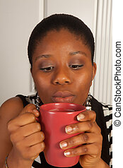Blowing on hot coffee - Young african woman blowing on her...