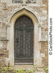Old dark Church door with a pointed stone archway set in stone