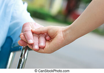 Senior women in wheelchair holding hands with caretaker