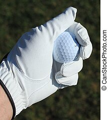 Golf ball in goved hand - a golf ball in a golfers gloved...