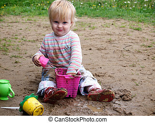 Dirty baby play with sand - bedraggled baby play with sand