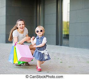 Fashion-monger baby on shopping with mom wear new glasses
