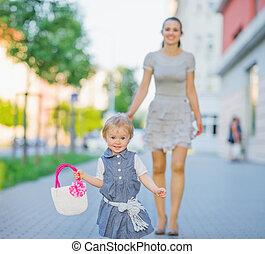 Happy baby walking with mom in city