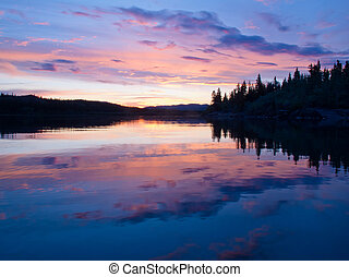 Reflection of sunset sky on calm surface of pond -...