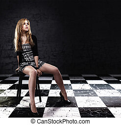 young woman in checked skirt sitting on a stool on checked floor with grey background