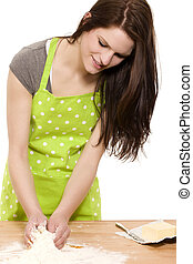 young happy woman mixing dough for baking on a table with...