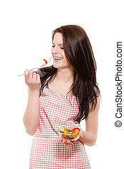 happy young woman with red apron eating salad on white background