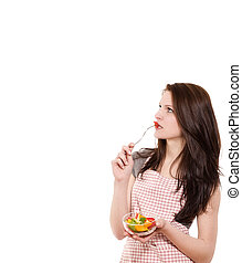 young woman from side eating salad looking up on white background