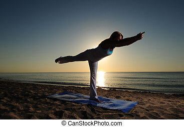 Warrior III yoga pose on beach - Woman doing yoga Warrior...
