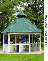Gazebo at park during summer with green grass and trees