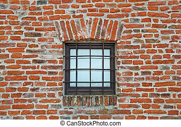 brick wall with iron lattice window of an ancient prison -...