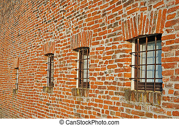 red brick wall with iron lattice window of an farm - red...
