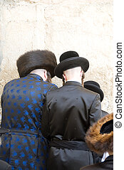 Hasidic Chassidic Jews wearing traditional clothing praying at The Western Wall Jerusalem Israel Palestine