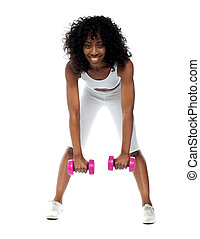 Fit woman exercising. Bending down holding dumbbells