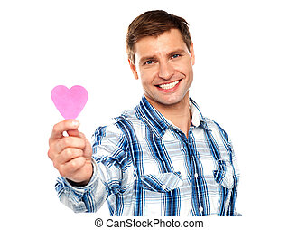 Man showing pink paper heart shaped cutting against white...