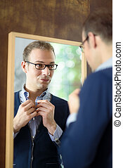 Young man dressing up and looking at mirror - Portrait of...