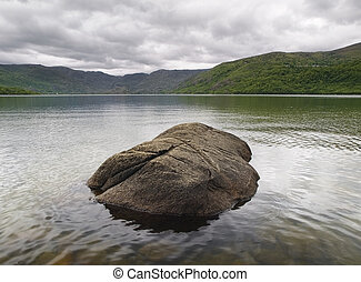 A lake with a rock in the middle. The photo is taken in the...