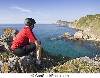 Cyclist sitting, staring at a coastal landscape on a sunny...
