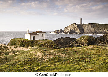 Coastal landscape with chapel and lighthouse. The chapel is...