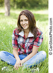 Beautiful teen girl in the park at green grass