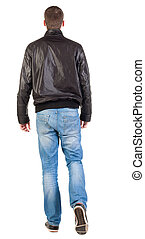 Back view of walking handsome man in jacket. going young guy...