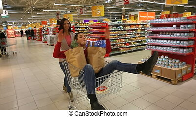 Ready, steady, go - Young people taking a ride in a shopping...