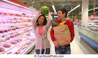 Cute shoppers - Lively young couple doing shopping and...