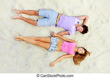 Sleep on the beach - Above angle of two teenage friends...