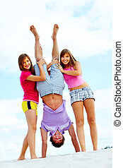 Fun on the beach - Portrait of happy teenage girls holding...