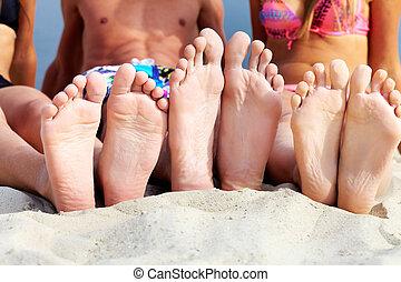 Getaway - Soles of teenagers sunbathing on sandy beach