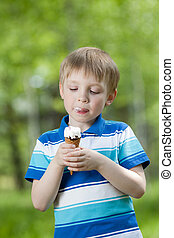 young child eating a tasty ice cream outdoor