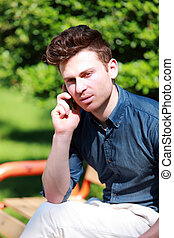 Young man at telephone in nature
