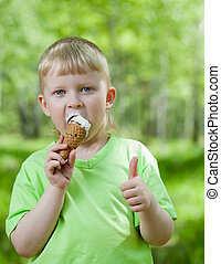 kid eating a tasty ice cream outdoor and showing thumb up
