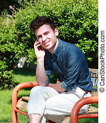 Relaxed handsome man in park calling