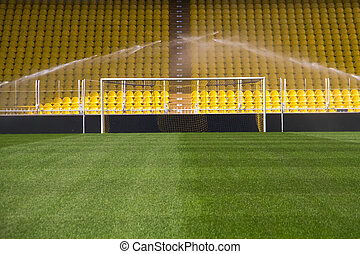 Empty stadium goal and sprinklers - Sprinklers are washing...