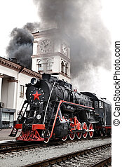 Old steam train is leaving a station. Vintage Steam engine...