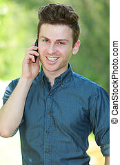 Portrait of handsome man with telephone in park