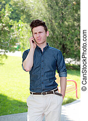Unhappy man in park on telephone