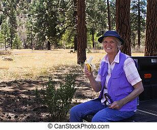 Octogenarian woman enjoying forest - Mature woman enjoying...