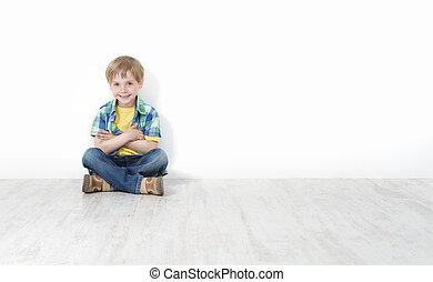 Handsome little boy sitting on floor leaning against white...