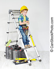 Little boy handyman with helmet and tool belt on stepladder. Equipment for construction works