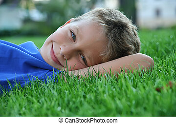 Young boy laying on the grass