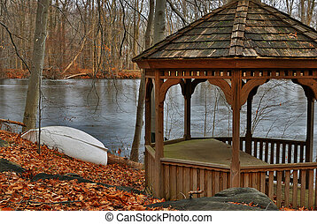 The wooden arbor on the bank of the stood lake, a white boat...