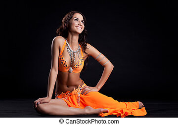 Smiling oriental dancer in orange costume