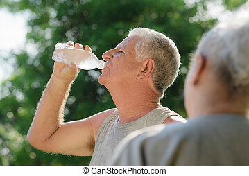 Seniors drinking water after fitness in park - Senior...