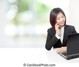 business woman speaking phone and using computer - Young...
