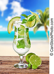Mojito drink with blur beach on background